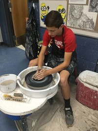 picture of student throwing on the wheel
