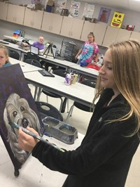 picture of student painting on canvas