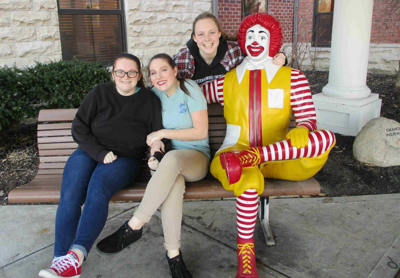 Students sitting with Ronald McDonald on bench