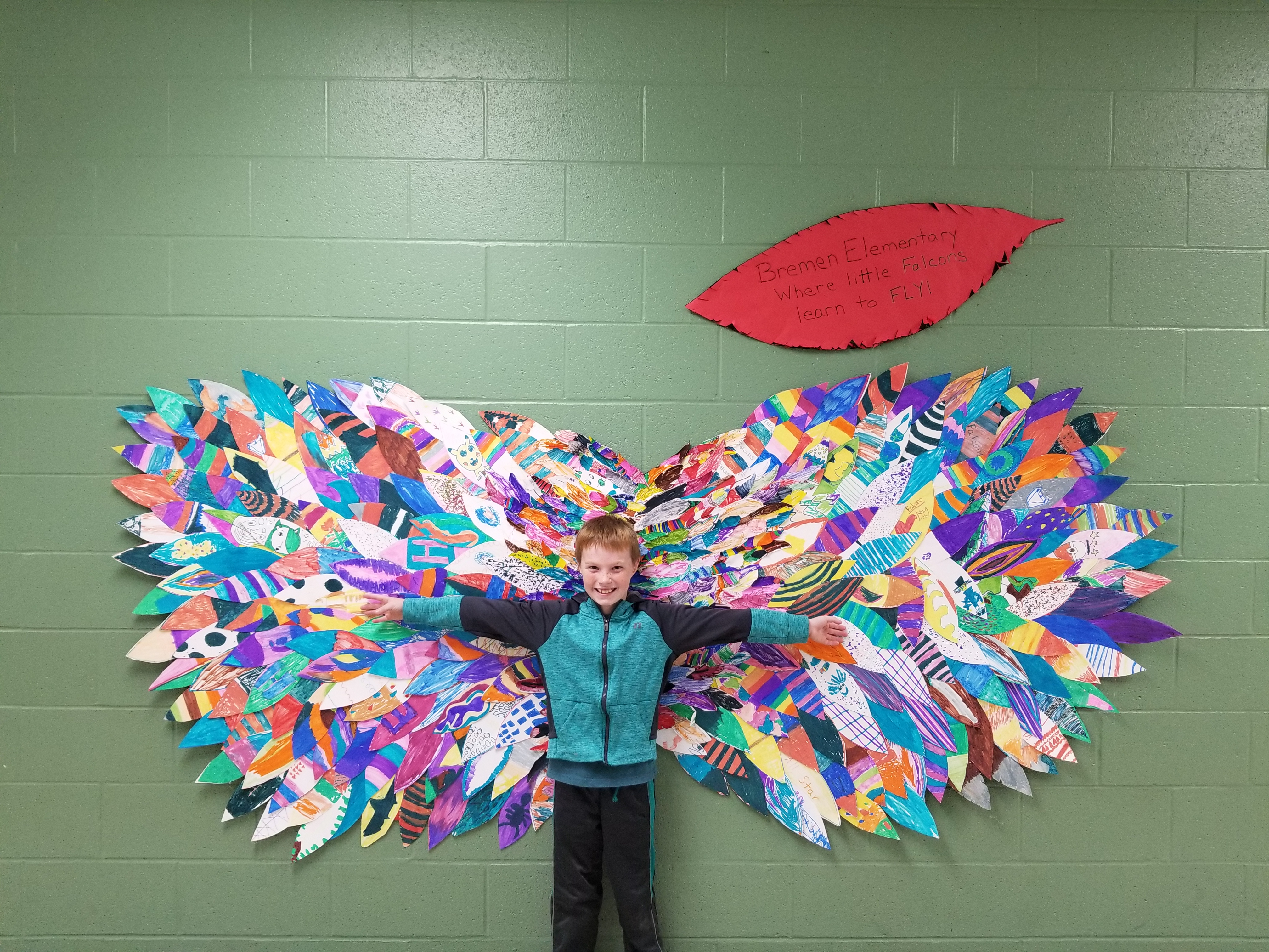student standing in front of the falcon wings
